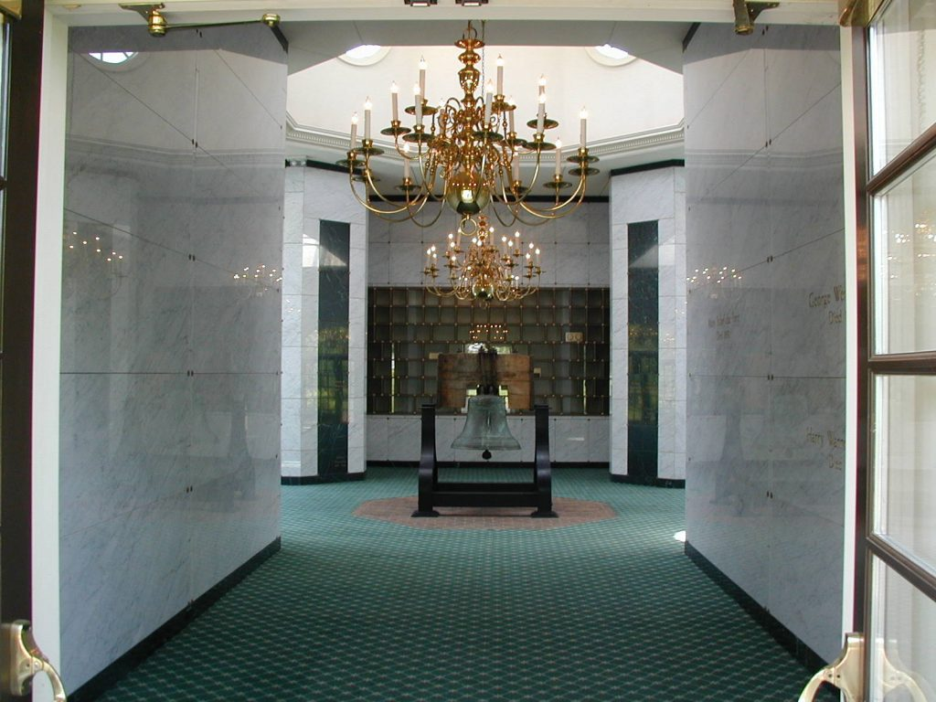 image of indoor crypts at Arlington Cemetery - marble walled room with green carpet and a large chandelier